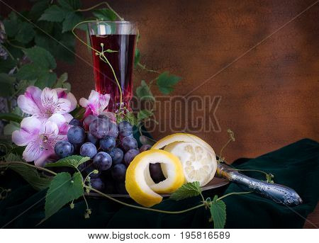 Still life in antique style with glass of wine pink flowers grapes and lemon on pewter plate with copy-space