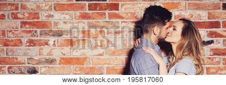 Couple Kissing Against Brick Wall