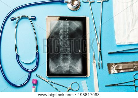Tablet pc and doctor tools on blue surface. Medical concept