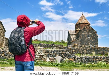 Woman with backpack taking photo of ancient monastery in Armenia using smartphone