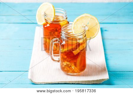 Iced tea in a glass jar with lemon on blue wooden background.