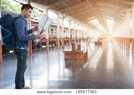 Asian Man With Backpack Standing On Platform At Train Station. Backpacker Or Traveler Look At Map Wh