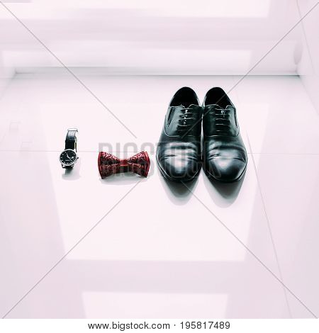 Groom's shoes, bow tie and watch on light background. Preparation for wedding concept.