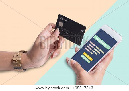 Woman Hold Credit Card With Mobilephone On Pastel Background