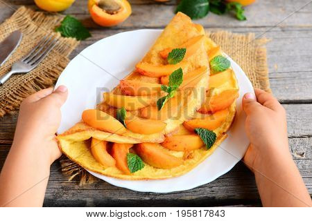 Child holds a plate with an omelette in his hands. Child prepared a simple stuffed omelette with apricots. Children in kitchen. Rustic style