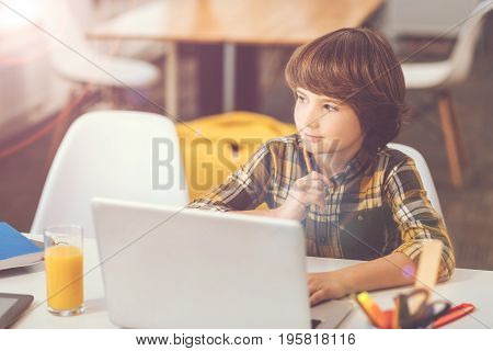 Modern device. Thoughtful nice pleasant boy sitting in front of the laptop and holding a pencil while thinking about his home task