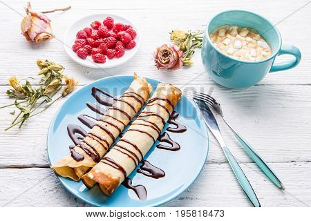 Homemade pancakes or russian blini with chocolate sauce on plate on white wooden background. Top view