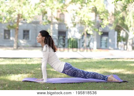 Sporty attractive young woman practicing yoga on a nature background. Woman is doing fitness outdoor. Fitness, workout, healthy living and diet concept. An attractive and calm woman doing pilates yoga