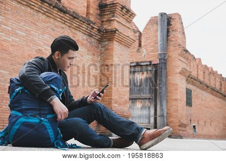 Young Traveler, Asian Man Wearing Black Jacket And Blue Jeans Sitting Near Old Orange Brick Wall Wit