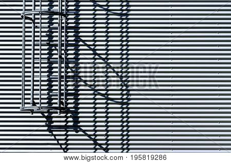 Corrugated metal wall with fire escape ladder. Metallic background texture. Safety and security concept.