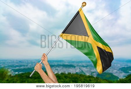 Young man's hands proudly waving the Jamaica national flag in the sky, part 3D rendering