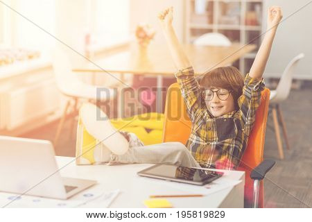 Homework is done. Delighted positive pleasant kid holding his hands up and relaxing while finishing his home task