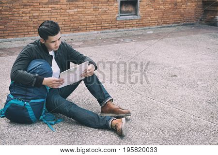 Young Traveler Reading Map. Asian Man Wearing Black Jacket And Blue Jeans Sitting Near Old Orange Br