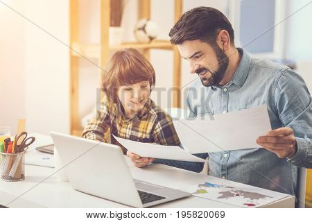 I need help. Pleasant caring handsome father sitting with his son at the table and holding two sheets of paper while helping him with school homework