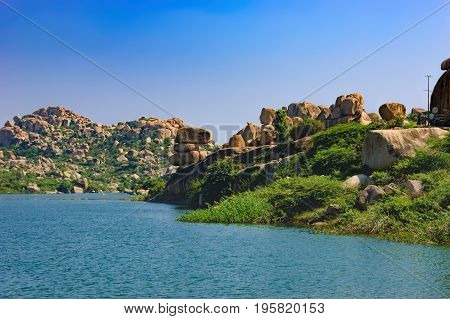 Blue waters of the Tungabhadra River in Hampi, India. River landscape with picturesque rocks on the shore tropical nature and the road to the ancient ruins across the bridge