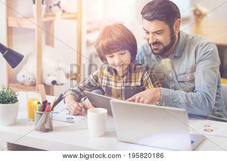 Look here. Happy delighted good looking man sitting with his son and pointing at the tablet screen while using modern technology