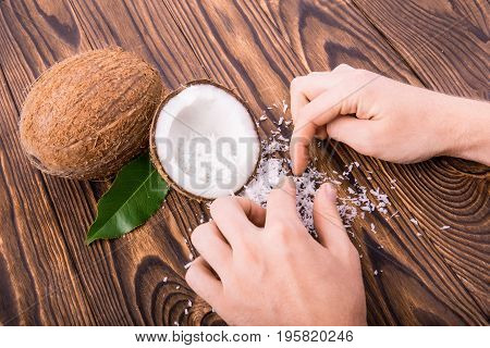 Two big, whole and crushed in a half coconuts with bright green leaves and coconut flakes on a dark brown wooden background. Men's hands collect coco chips. Exotic coconut products. Tropical fruits.