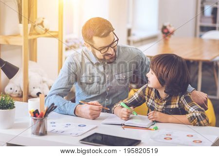 Time together. Delighted positive smiling man sitting near his son and looking at him while holding a pencil