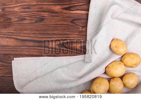Healthy and whole potatoes on a grey fabric and on a wooden table. Summer harvest. Uncooked new potatoes. A large pile of nutritious and young potatoes. Raw, fresh and organic vegetables.