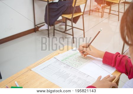 Asian Student hand holding pencil writing doing test examination and exams answer sheets in class room education exam concept