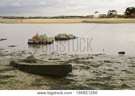 Ruin of a sunk boat in beach during the low tide with two floating platforms anchored