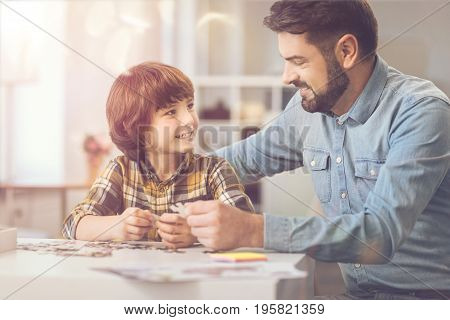Wonderful mood. Cheerful happy cute boy holding a jigsaw puzzle piece and smiling while looking at his father