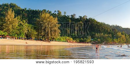 Khao Lak, Thailand - December 28, 2015: Tourists have a rest walk and watch the colorful sunset at Nang Thong Beach, Andaman Sea, Khao Lak, Thailand. Relaxing on paradise beach with palms trees