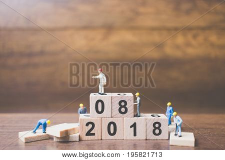 Miniature worker team building number on wooden block Happy new year 2018
