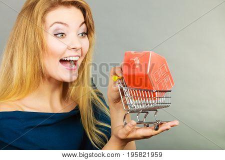 Buying property or home real estate investment concept. Happy woman holding shopping cart with house inside