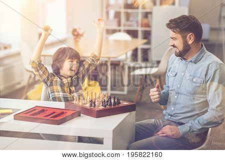 My victory. Cheerful smart delighted boy holding his hands up and laughing while winning the chess game