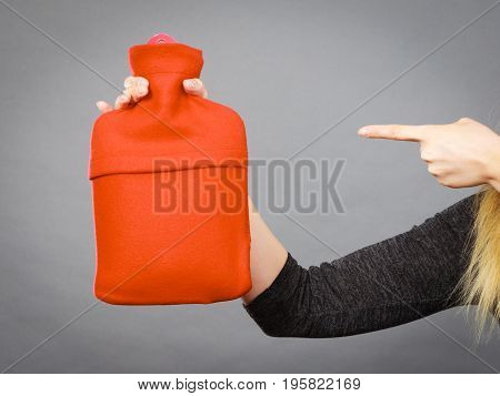 Woman pointing at warm hot water bottle in red soft fleece cover on grey. Health care pain relievers treatment objects concept.