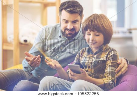 Look at it. Positive nice delighted boy sitting with his father and holding a smartphone while showing him an interesting picture