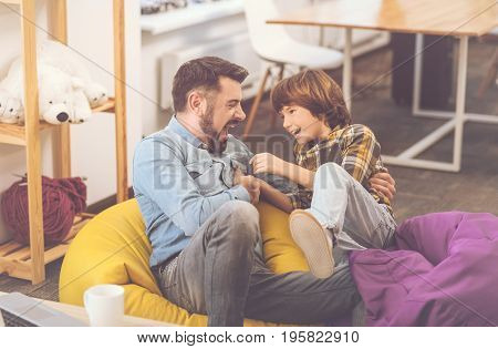 Great mood. Cheerful positive happy father and son looking at each other and laughing while enjoying their time together