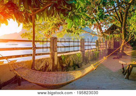 Hammock on corong beach on sunset. Tropical holidays in El Nido, Palawan, Philippines.