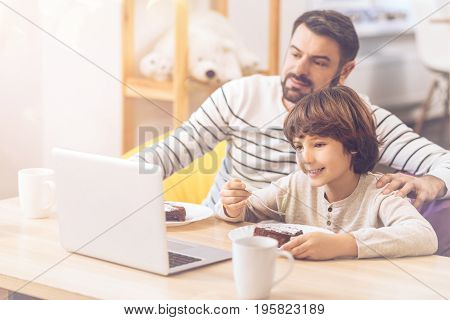 Interesting entertainment. Nice pleasant positive father and son sitting in front of the laptop and watching a movie while eating a cake