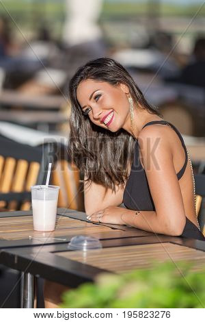 Perfect woman in the black dress sitting and smiling wide at the street cafe with milk cocktail on the street. Beauty portrait.
