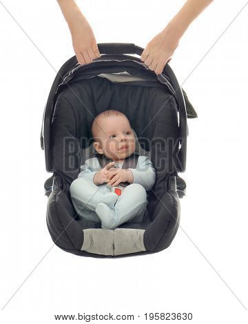 Hands holding adorable baby boy in car seat on white background