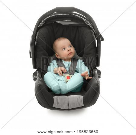 Adorable baby boy sitting in car seat with safety belt on white background