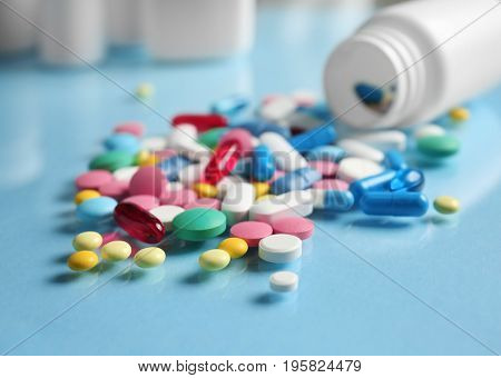 Plastic container and pills on color background