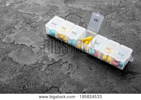 Plastic container with different pills on grey textured table