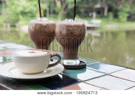 Hot Cappuccino Coffee Cup And Iced Chocolate Cocoa Drink In The Glass On Table At Cafe