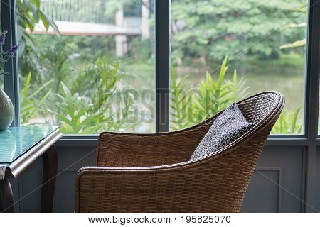 Rattan Chair With Pillow In Living Room In Modern House Beside Window Garden And Lake View. Home Int