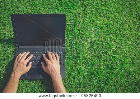 High angle view of man using blank screen laptop on grass. Technology and green energy concepts. Space for copy.