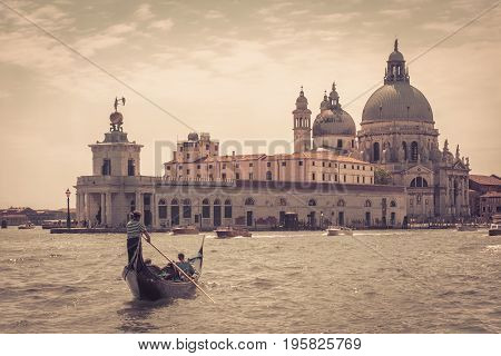 The gondola with tourists floats along the Grand Canal in Venice, Italy. Santa Maria della Salute church in the distance. Gondola is the most attractive tourist transport in Venice.