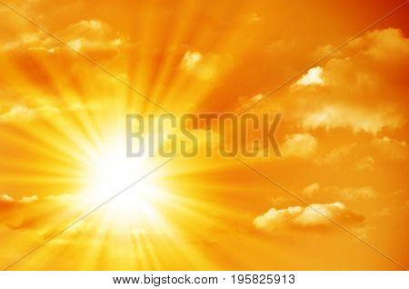 Bright sun in the orange sky with cumulus clouds