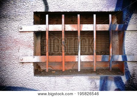 The closeup of a colorful painted basement with rusted iron bars.