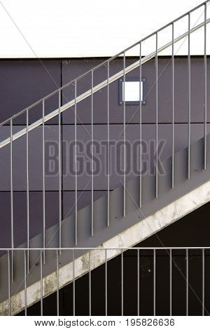 The detail of a modern staircase with a stainless steel railing and a wall light.