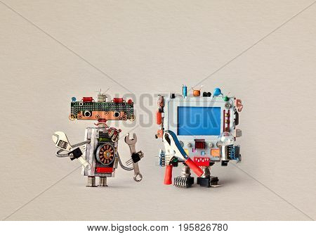 Robots maintenance fix service concept. Hand wrench adjustable spanner handyman. Robotic computer with red pliers blue empty display. Aged paper background.