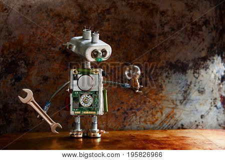Robotic toy character lamp in hand, rusty iron surface. Vintage textured wall backdrop. Shallow depth field