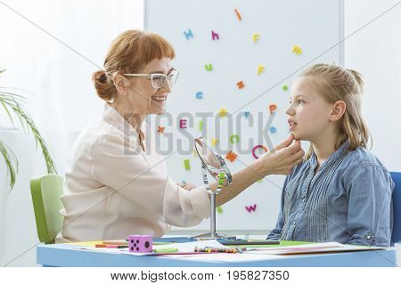 Speech Therapist Exercising With Child